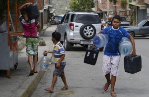 TO GO WITH AFP STORY by Gerardo Guarache Boys carry empty bottles and cans to fill them with water in Caucaguita, Caracas, on June 20, 2014. Water use in Caracas and its suburbs, home to five million people, is being rationed since the beginning of May and will continue for two more months, due to drought. Even when fully operating and unaffected by drought, water supply levels in the capital area are below international standards, capable of providing 340 liters per person per day, which is sufficient for household consumption but falls short of commercial and industrial demands. AFP PHOTO/Leo RAMIREZ